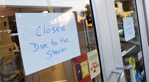 window of business with paper sign that says closed due to storm for Business Interruption Claims